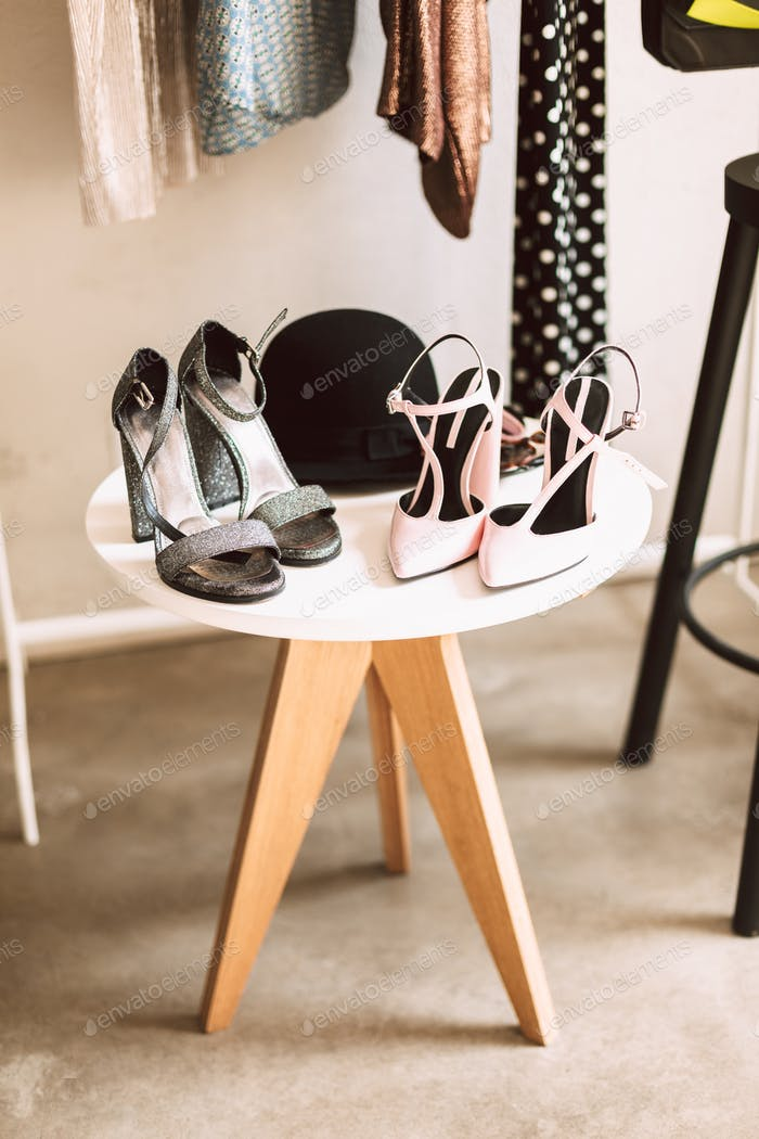 Close up shoes on heel and black hat on stand in showroom