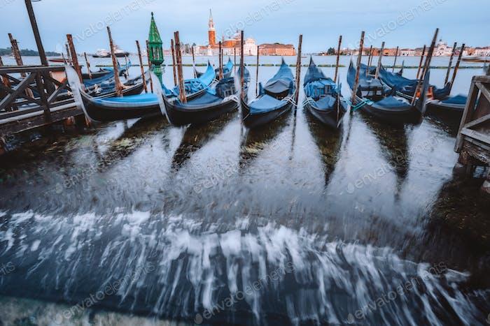 Gondolas floating in the Grand Canal in evening warm light, San Giorgio Maggiore church in