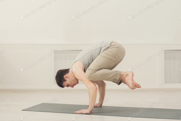 Young man standing in Bakasana exercise