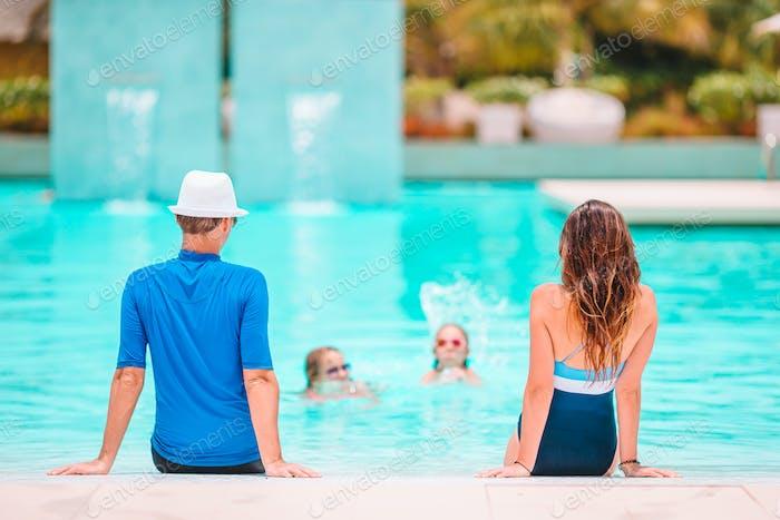 Família feliz de quatro em piscina ao ar livre