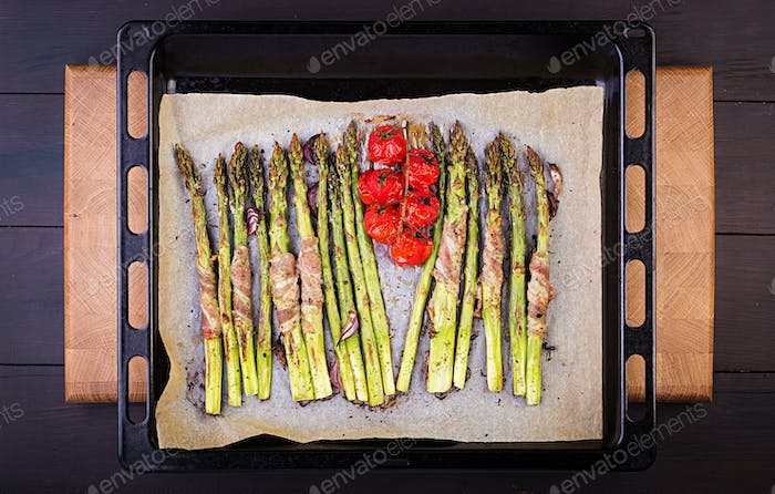 Grilled green asparagus wrapped with bacon on wooden table. Top view
