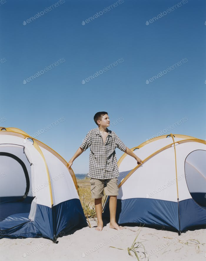 Adolescent boy standing by camping tents on beach