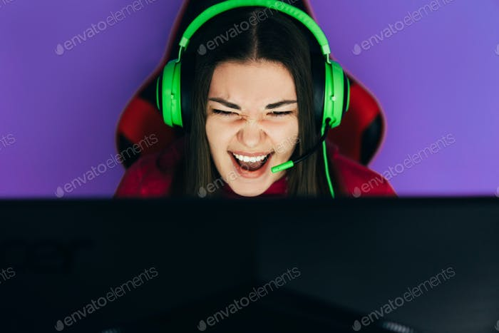 The gamer sits on a gaming chair and plays computer games. The player has green headphones on his
