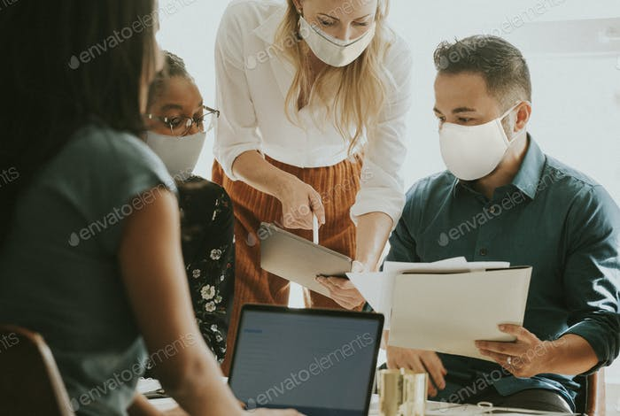 Geschäftsleute mit Gesichtsmasken bei einem Meeting