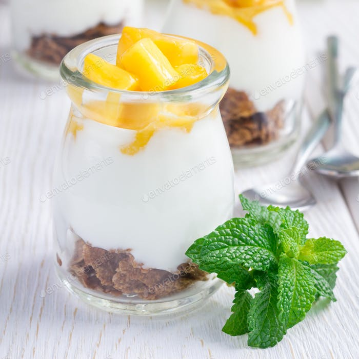 Breakfast dessert with bran flakes, plain yogurt and mango, square format