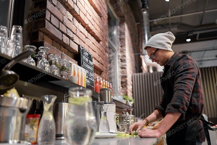 Mann oder Barmann kochen Smoothie im veganen Café