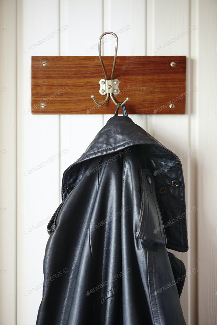 Classic male black leather jacket stored on a hanger. Vertical