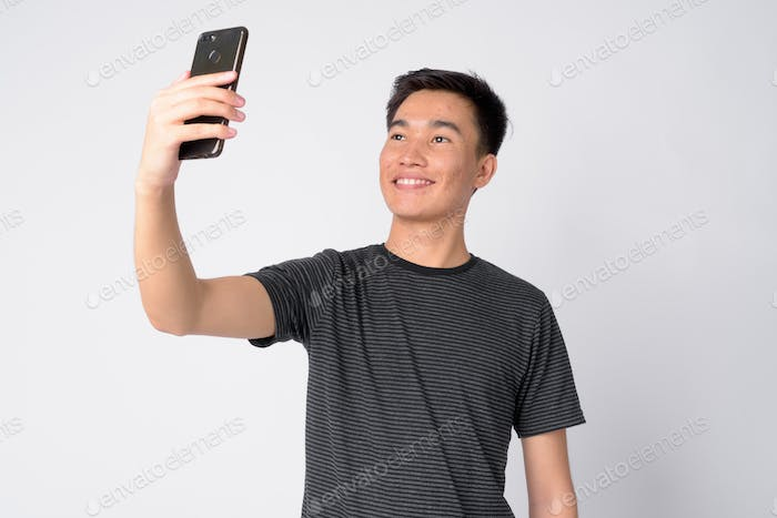 Portrait of young happy Asian man taking selfie