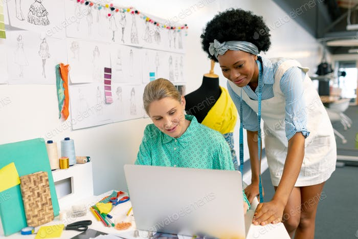 front view of diverse female graphic designers discussing over laptop in office