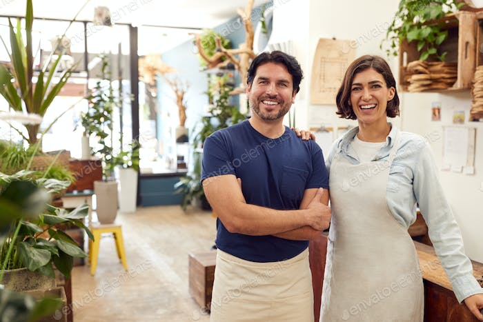 Portrait Of Smiling Male And Female Sales Assistants Standing By Sales Desk Of Florists Store