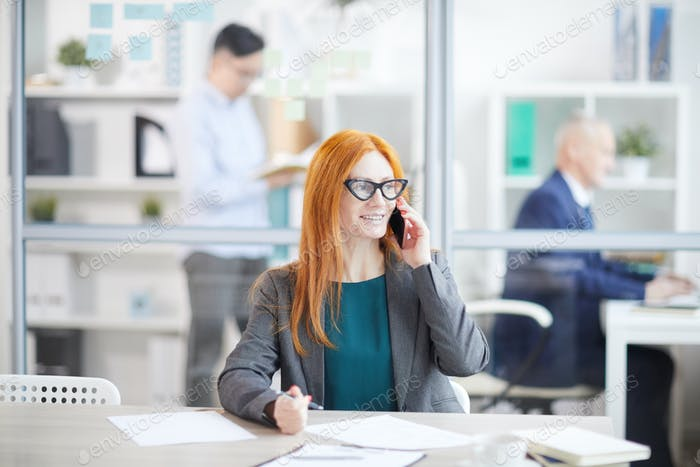Female Manager Speaking by Phone in Office