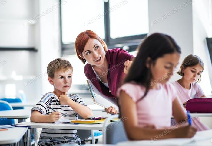 Ein Lehrer, der unter kleinen Schulkindern auf der Lektion geht, erklärt.