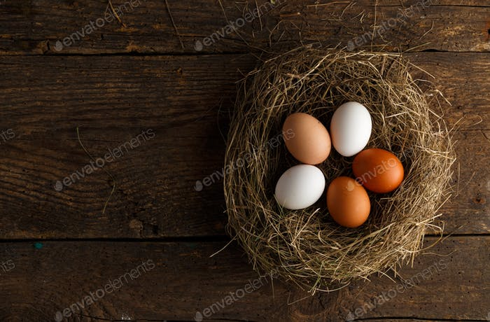 Fresh chicken eggs in a nest on a wooden background