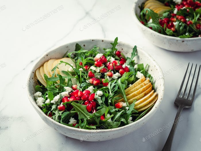 salad with arugula, pear, pomegranate and cheese