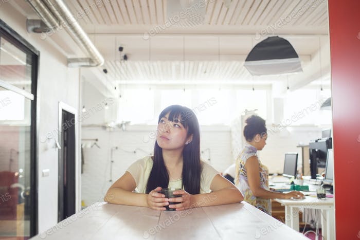 Women at office, one working, other holding glass