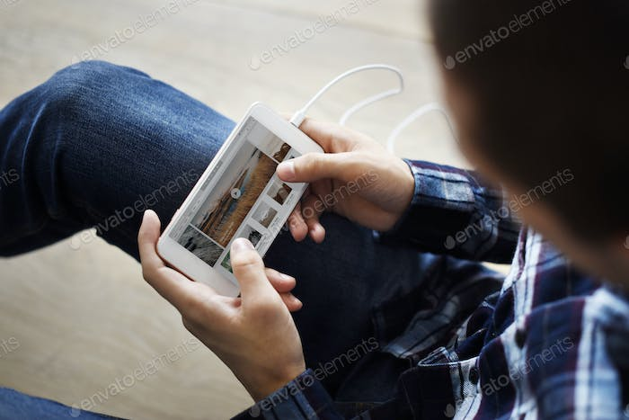 Man using a smartphone and music playlist on the screen