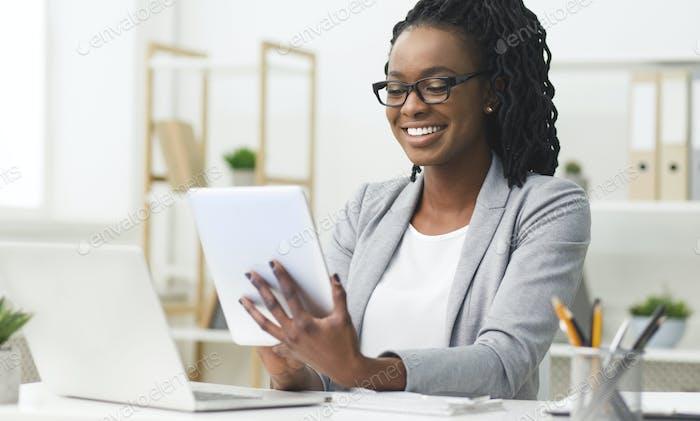 Afro Business Lady mit digitalem Tablet und Laptop im Büro