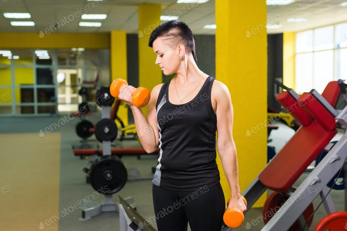 Strong fit girl exercising with dumbbells