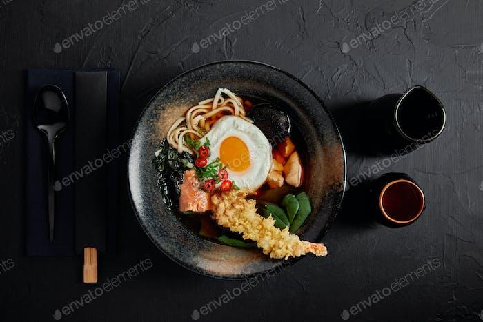 Draufsicht auf Schüssel mit japanischer Gourmetsuppe mit Ei, Nudeln und Pilzen