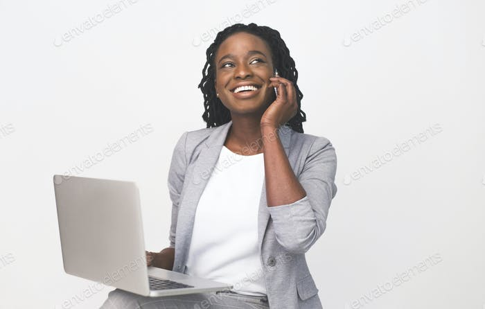 African American Businesswoman Talking On Phone Working On Laptop, Isolated