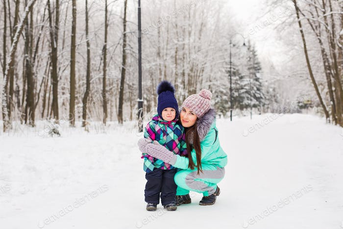 happy mother and baby in winter park. family outdoors. cheerful mommy with her child