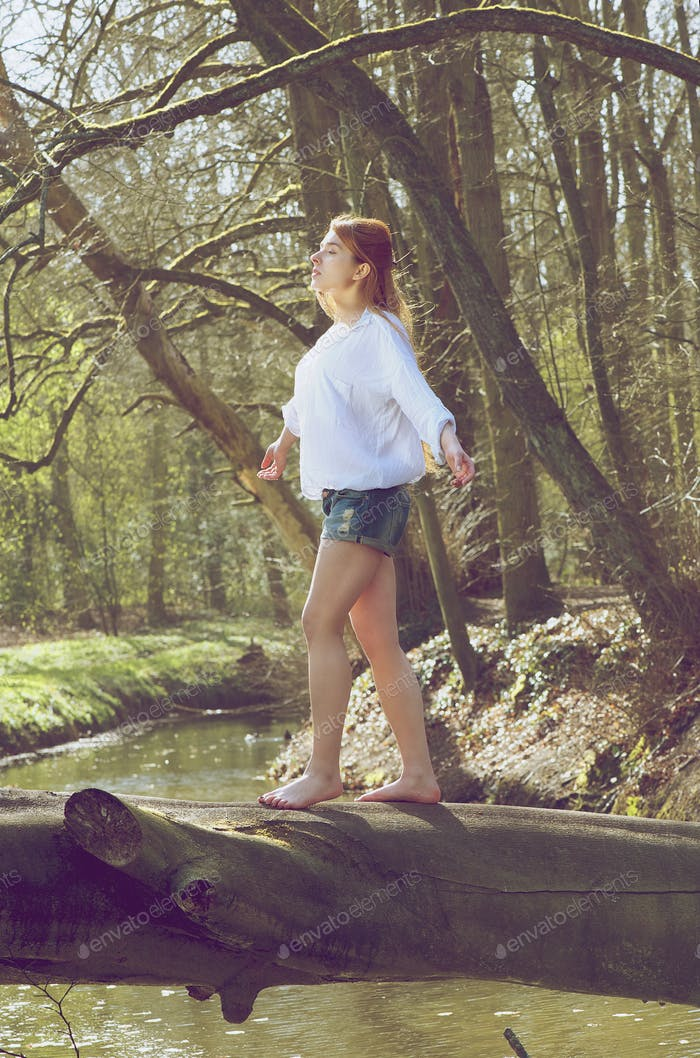 Portrait of a young woman balancing on fallen tree trunk across stream