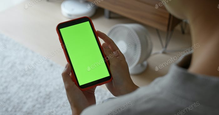 Woman hold mobile phone with green screen at home