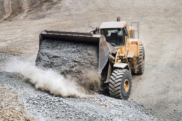 Industrielle schwere Planierraupe bewegt Kies auf Autobahnbaustelle