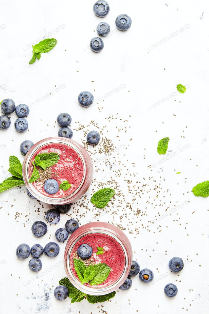 Pink smoothie with blueberries, chia seeds and mint leaves in glass jars