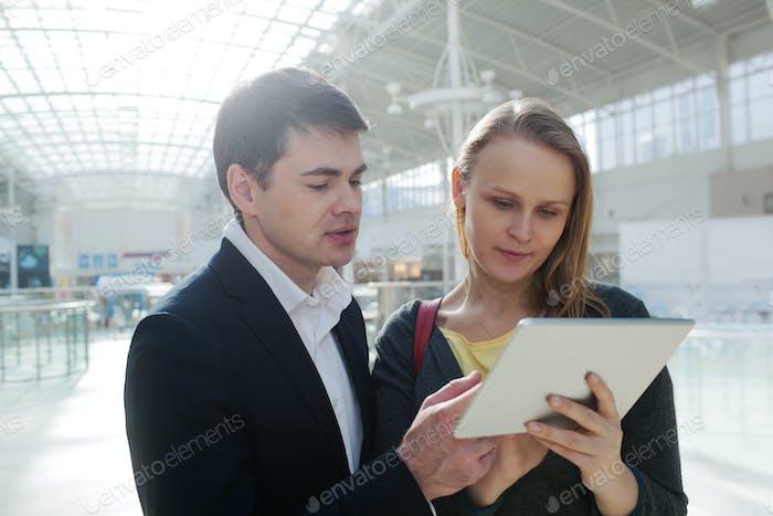 Junge Geschäftsleute mit Unterlage im Einkaufszentrum