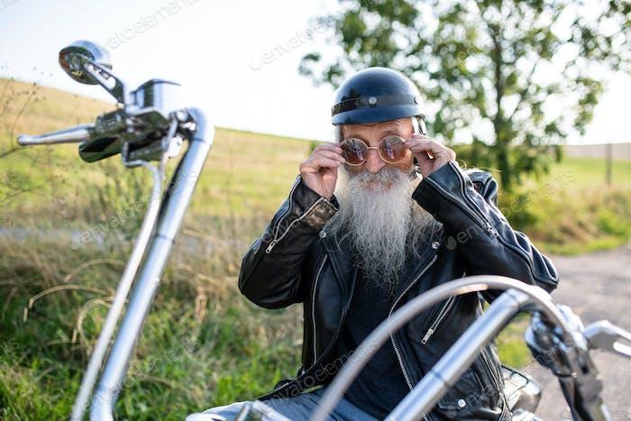 Старший человек путешественник с мотоциклом и солнцезащитные очки в сельской местности