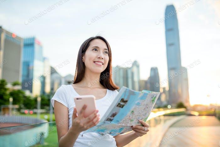 Mujer con el celular y el mapa de la ciudad en Hong Kong