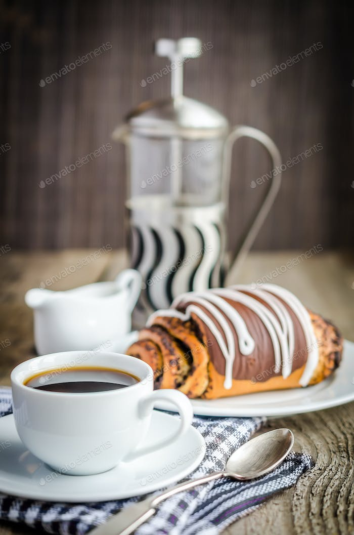 Cup of coffee and poppy bun glazed with ganache