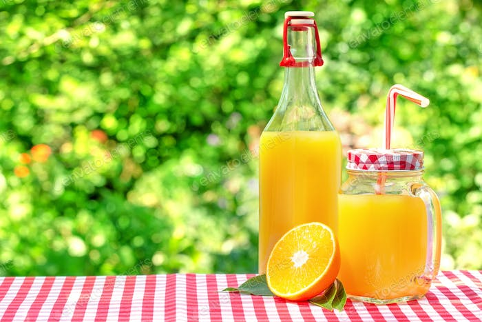 Glass jar and a bottle with orange juice