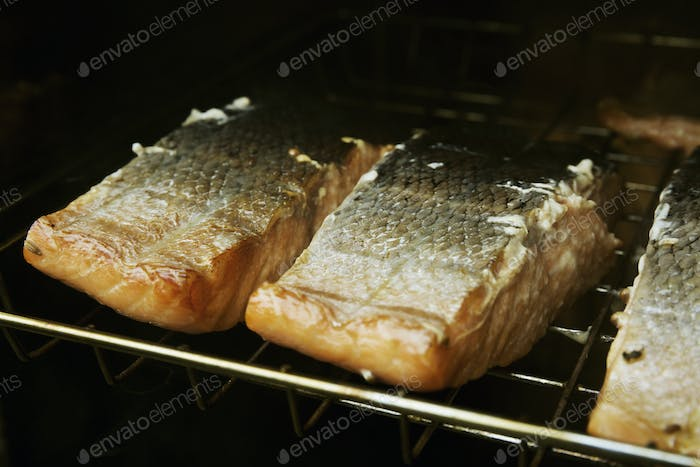 Close up of fish fillets on a rack in a fish smoker.