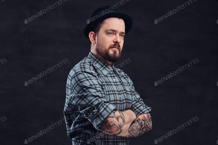 Portrait of a tattooed handsome middle-aged man in a studio