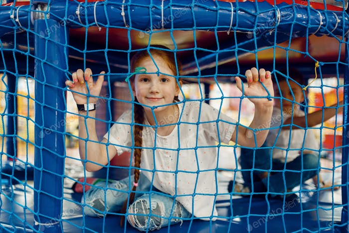 Girl behind the grid in the game maze, playground