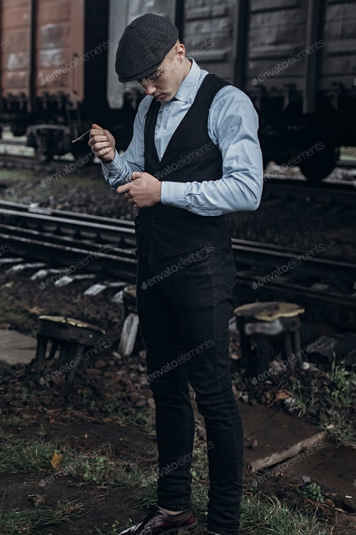 Stylish man in retro look smiling posing on background of railway