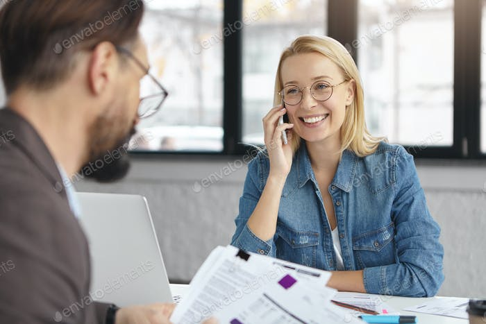 Portrait of blonde smiling female manager has phone conversation, looks joyfully at her partner who
