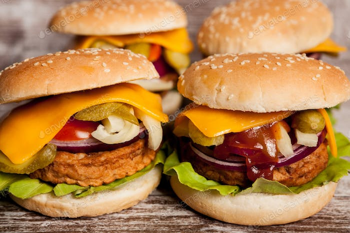Four Delicious home made burgers on wooden plate