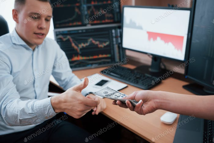 Woman's hand giving money. Day of salary in the modern office with screens with graphs on them