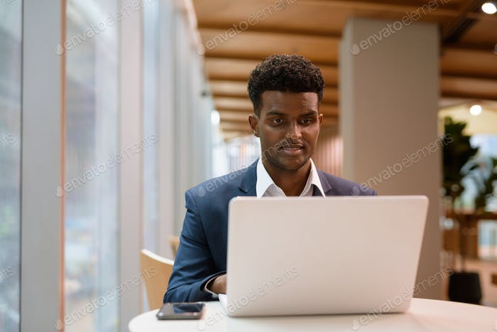 Portrait of African businessman using laptop computer in coffee shop
