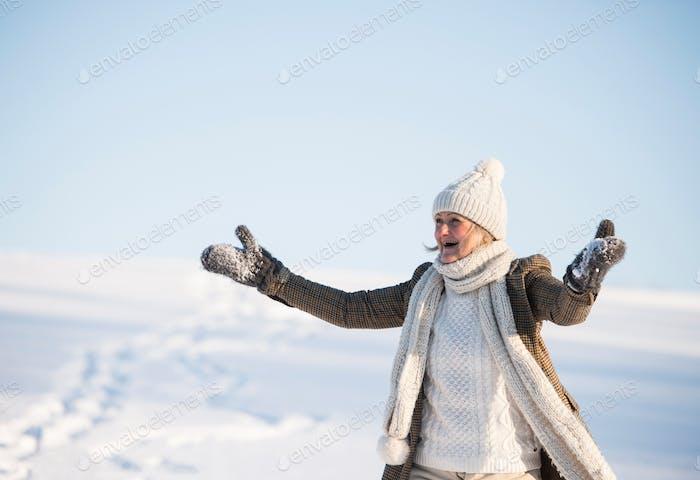 Beautiful senior woman on a walk in sunny winter nature