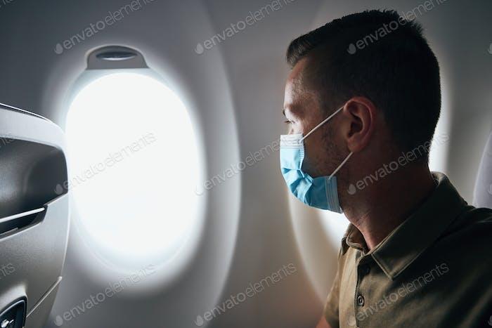 Mann trägt Gesichtsmaske im Flugzeug