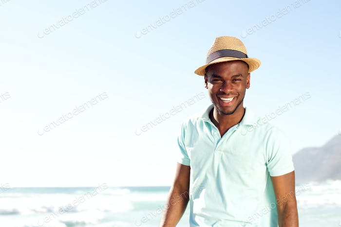 Cool young african man with hat at the beach