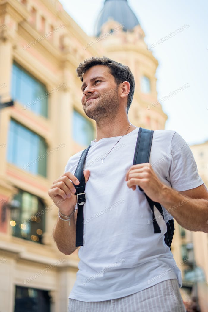 Happy tourist with backpack in city