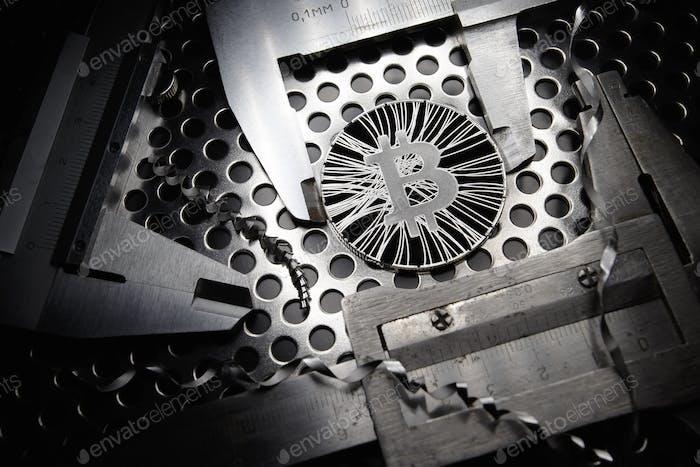 Bitcoin gemessen mit Messschieber auf Metallhintergrund. Konzept der internationalen virtuellen Kryptowährung
