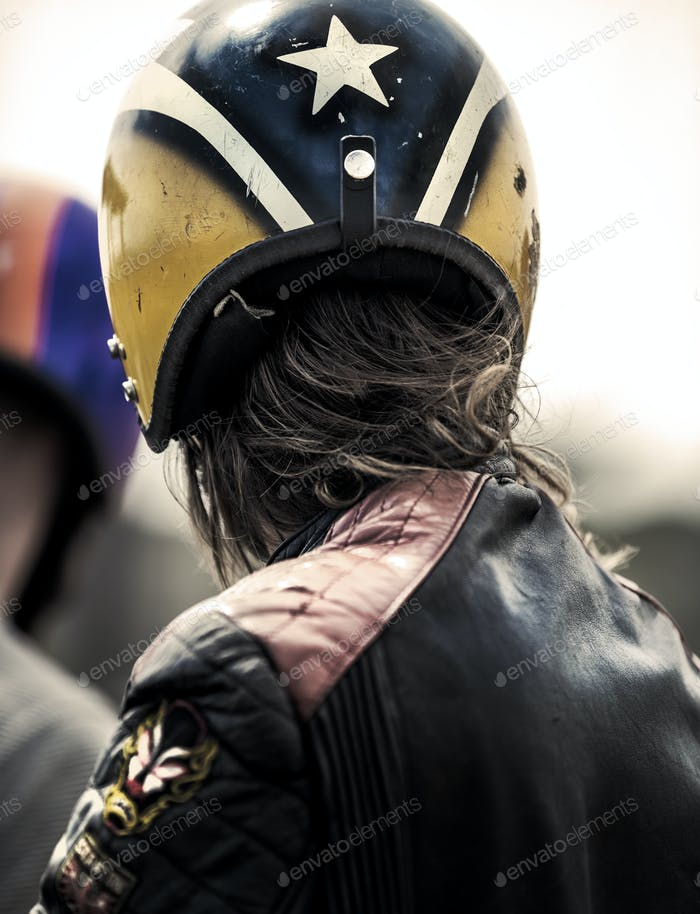 Rear view of man wearing yellow and blue crash helmet and black leather jacket.