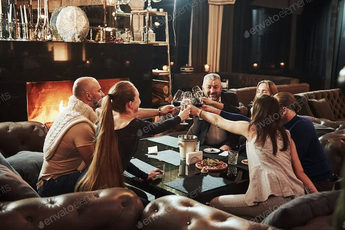 Knocking glasses. Family friends have nice evening near the fireplace in luxury modern restaurant