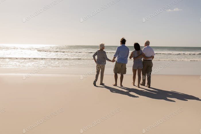 Rear view of family walking on beach in the sunshine